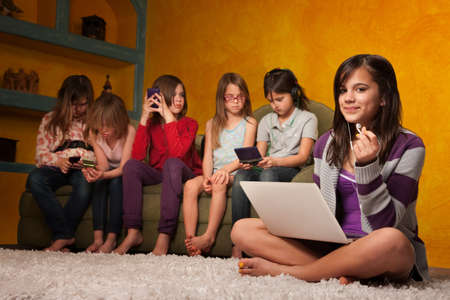 little girl barefoot: Caucasian girl with laptop while friends are busy with handheld devices Stock Photo