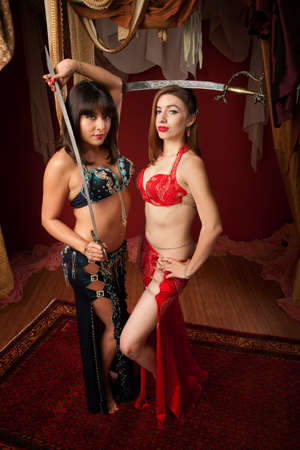 Two Sexy Belly Dancers balance traditional dragon swords photo