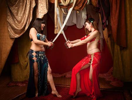 Two beautiful Arab belly dancers sword fighting Imagens