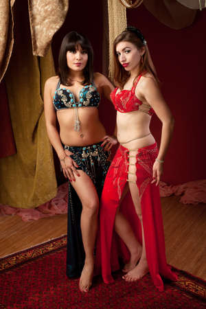 Pair of gorgeous belly dancers with hands on thighs photo