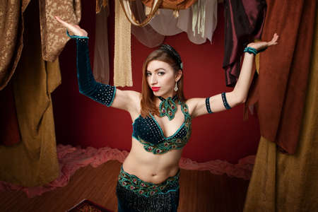 Beautiful belly dancer in green dress with palms up photo