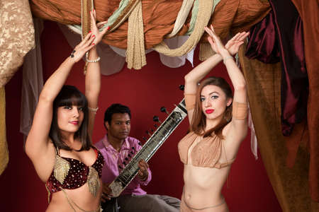 Two beautiful Arab belly dancers with Indian man playing Sitar photo