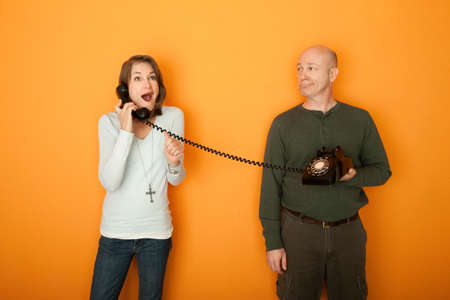 Excited Caucasian woman on telephone call with a middle-aged man on orange background Stock Photo - 9382005