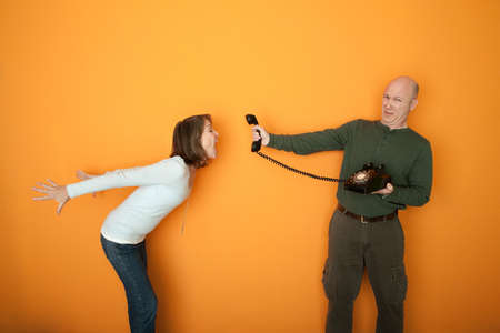 customer: Middle-aged man holds telephone while woman screams at it