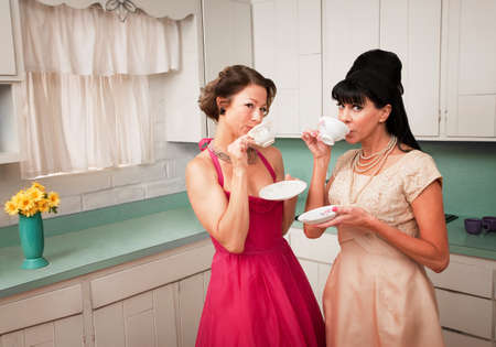 bouffant: Two retro-styled women drinking coffee in kitchen Stock Photo