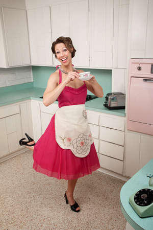 kitchen aprons: Middle-aged Caucasian woman standing on one foot in kitchen