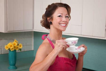 donna che beve il caff�: Donna di mezza et� felice bere il caff� in cucina