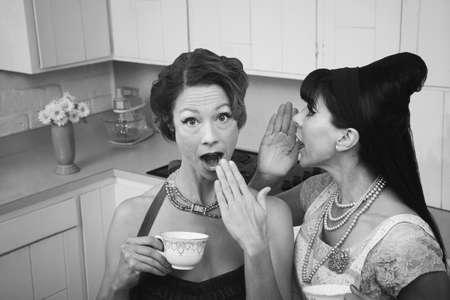 Woman whispers secret into a friends ear photo