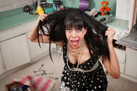 Ama de casa desesperada tirando su cabello en una desordenado cocina Foto de archivo - 9381991
