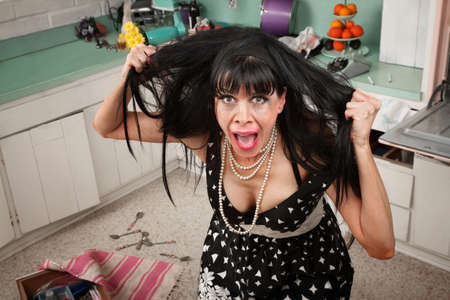messy: Desperate housewife pulling her hair in a messy kitchen