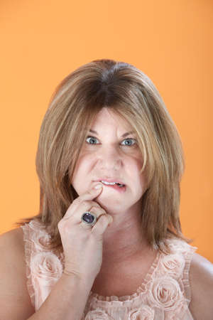 conundrum: Worried middle-aged Caucasian woman on orange background