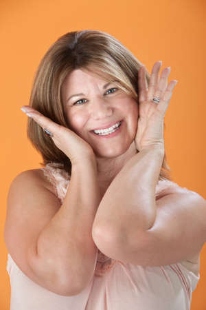 nightgown: Happy middle-aged Caucasian woman with hands on face