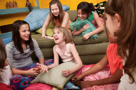Excited Caucasian girl with her happy friends at a sleepover photo