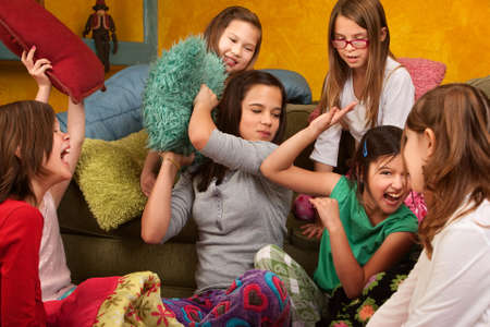 sleepover: Group of little girls hitting each other with pillows Stock Photo