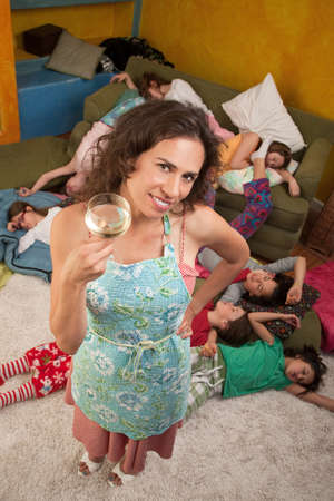 sleepover: Relieved Hispanic woman drinking wine after kids fall sleep