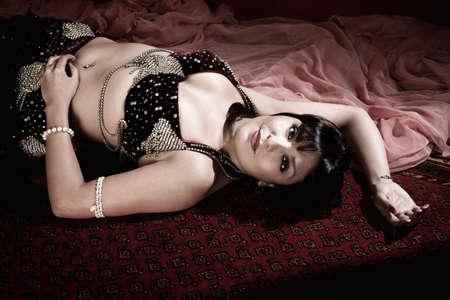 belly dancer: Beautiful Arab belly dancer lying down on carpet