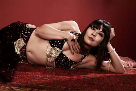 Beautiful Hispanic belly dancer lying down with hand on chest Stock Photo - 9611072