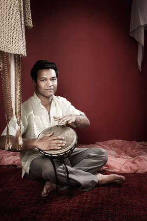 Young Handsome Indian man plays a tabla photo