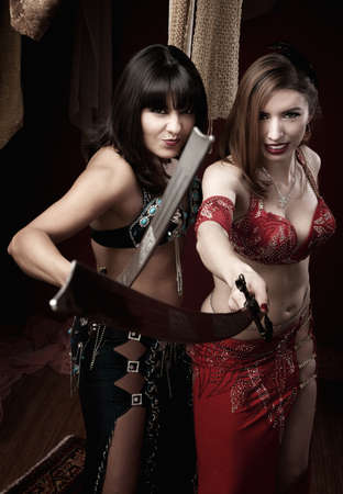 Two beautiful belly dancers hold traditional swords  photo