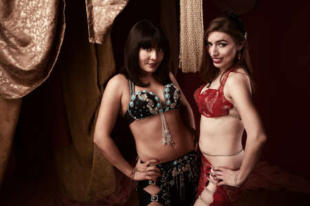Two beautiful belly dancers with hands on hips photo