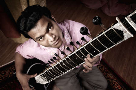 Birds-eye view of a hndsome young Indian man playing a sitar Stock Photo - 9610933