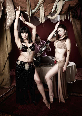 Two gorgeous belly dancers with a handsome Indian Sitar player behind them photo