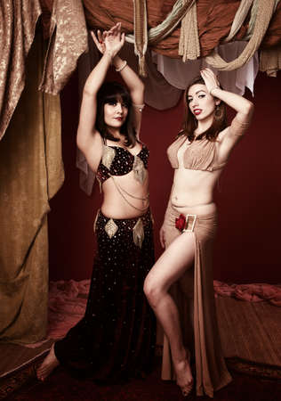 bellydancing: Two beautiful belly dancers with raised hands