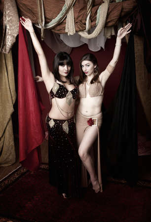 Two gorgeous belly dancers lift up red and black cloths photo
