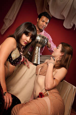 harem: Two beautiful belly dancers look at a handsome Indian tabla player Stock Photo