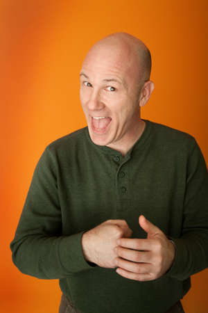 perplex: Happy middle-aged bald Caucasian man puts fist in his hand Stock Photo