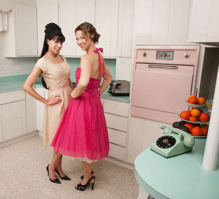 Happy Caucasian housewives in a retro kitchen with hand on hips  스톡 콘텐츠