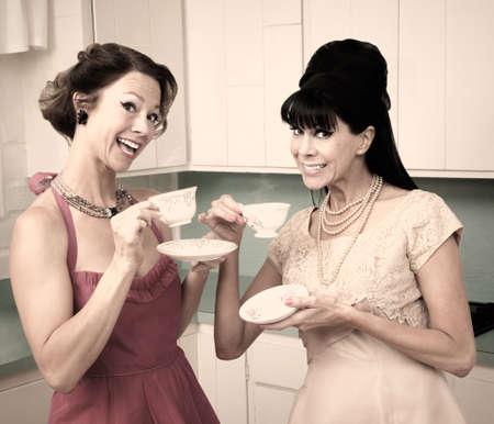 fake smile: Two retro style women enjoying tea in the kitchen