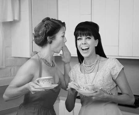 bouffant: Caucasian woman whispers joke to friend in her kitchen