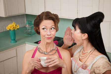 nosey: Retro styled woman whispers secret into friends ear