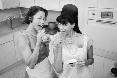 Two women smoke cigarettes while having coffee in a retro kitchen scene Stock Photo - 9610986