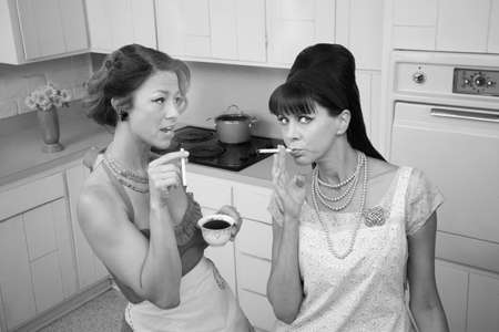 Two middle-aged retro styled women smoking cigarettes and having coffee  photo