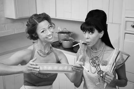 Happy housewife shows her smoking friend a dish in the kitchen photo