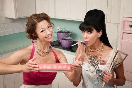 bouffant: Happy housewife shows her smoking friend a dish in the kitchen