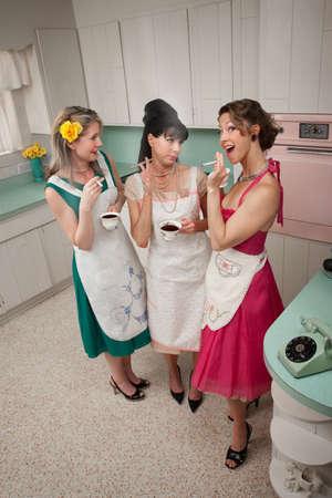 retro woman: Three women gossiping in a kitchen while smoking cigarettes Stock Photo