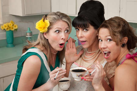 Three shocked women smoking and having coffee