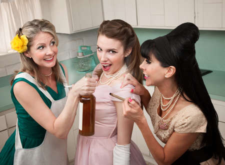 Young woman goes along with friends to smoke and drink in a kitchen