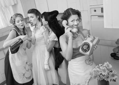 retro woman: Woman on phone while friends give young woman cigarette and alcohol in a retro styled kitchen scene