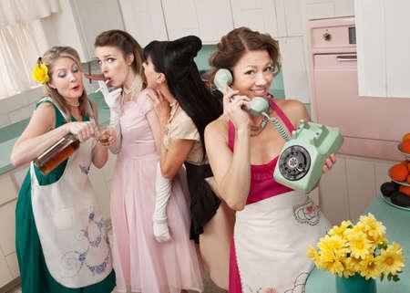delantal: Mujer de tel�fono mientras amigos dan joven cigarrillos y alcohol en una escena de cocina estilo retro