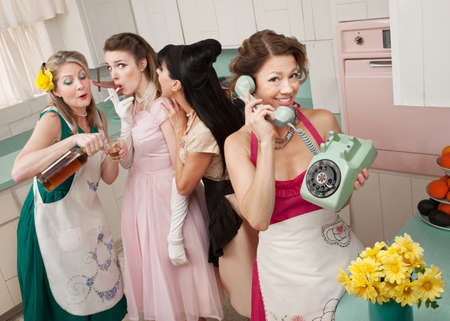 peer to peer: Woman on phone while friends give young woman cigarette and alcohol in a retro styled kitchen scene