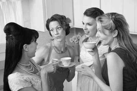 bouffant: Four retro-styled women chit-chat over coffee in a kitchen