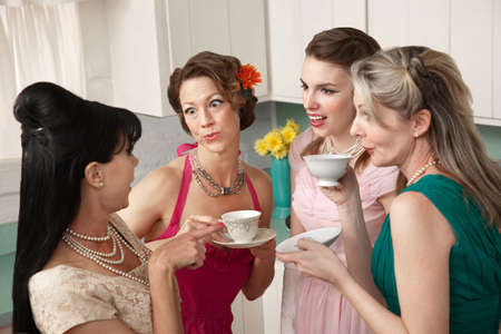 Four retro-styled women chit-chat over coffee in a kitchen photo