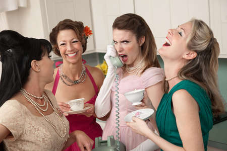 Outraged woman on phone with three friends in a kitchen photo
