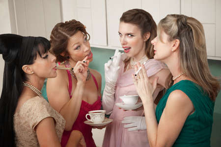 Four retro-styled women smoking cigarettes and drinking coffee in a kitchen