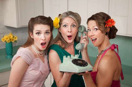 Three surprised women holding a rotary telephone in a kitchen