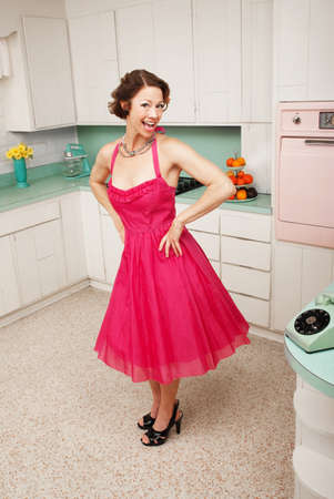 retro kitchen: Happy middle-aged woman with hands on hips in retro-styled kitchen scene Stock Photo